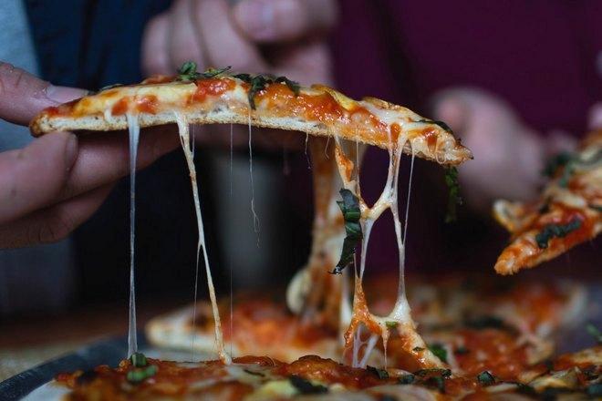 Аппетитный сыр тянется за кусочком пиццы