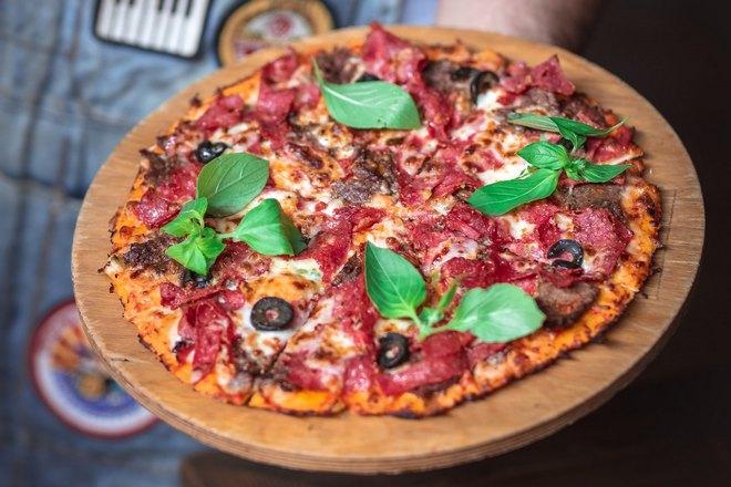 Пицца на круглом деревянном подносе