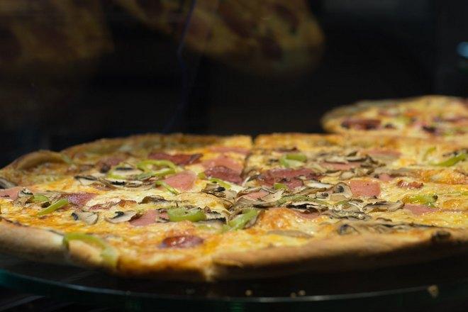 За первой пиццей виднеется вторая