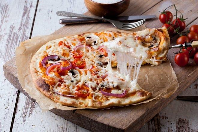 Сыр аппетитно тянется за кусочком пиццы