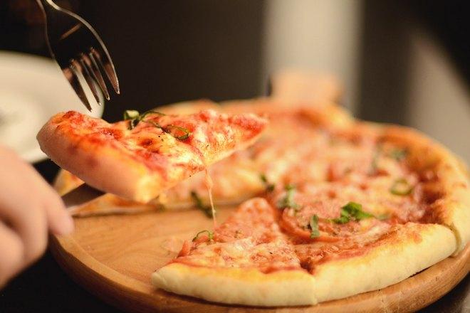 Берем вилкой кусочек пиццы