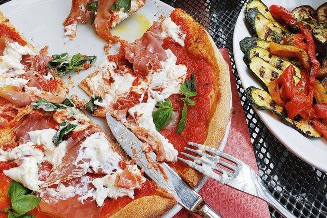 Пицца в тарелке с вилкой и ножом