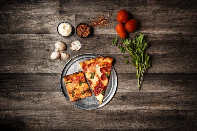 Пицца в окружении овощей и зелени