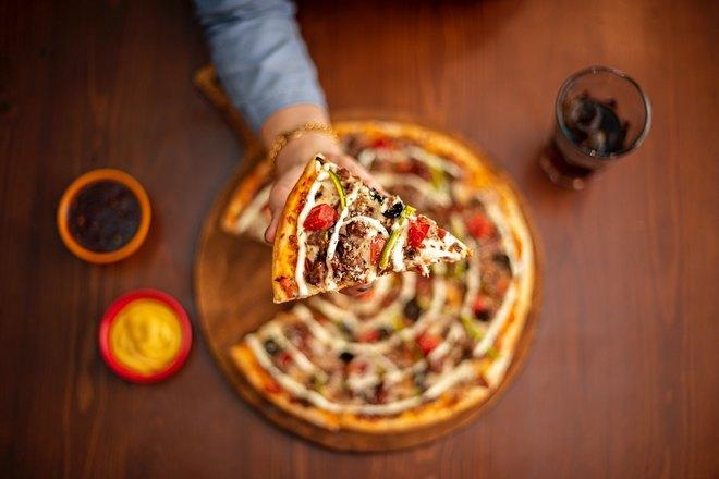 Кусочек пиццы подняли над столом