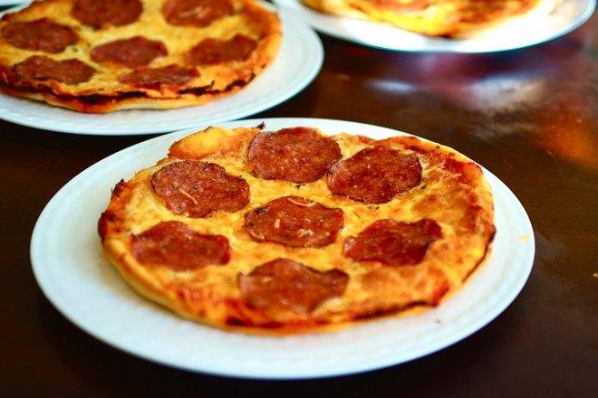 Пицца на тарелке, а рядом еще две пиццы