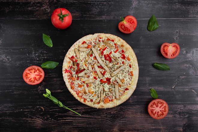 Пицца с сыром украшена помидорами