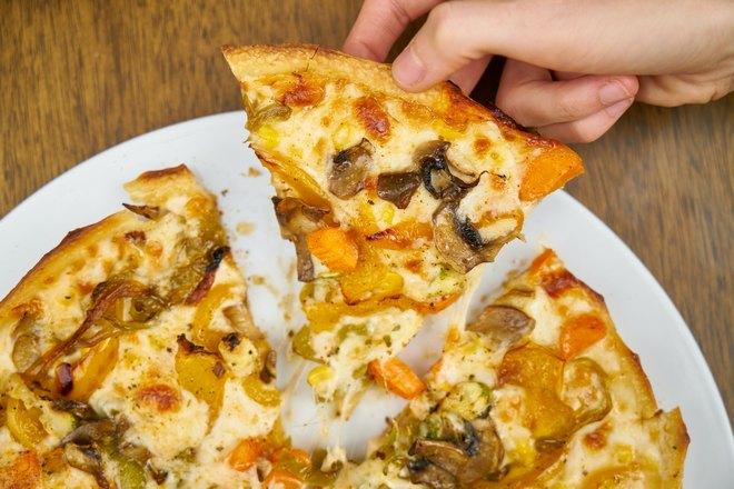 Кусок пиццы в правой руке