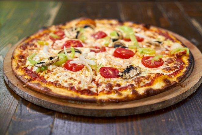 Пицца подана на круглом подносе