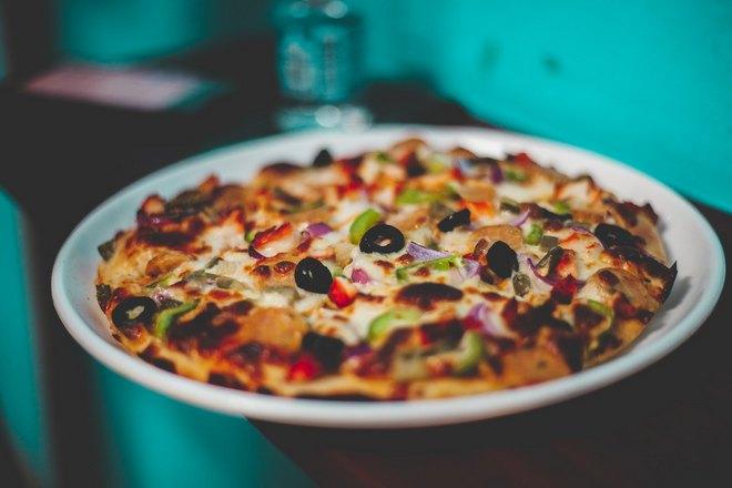 Румяную пиццу положили на тарелку