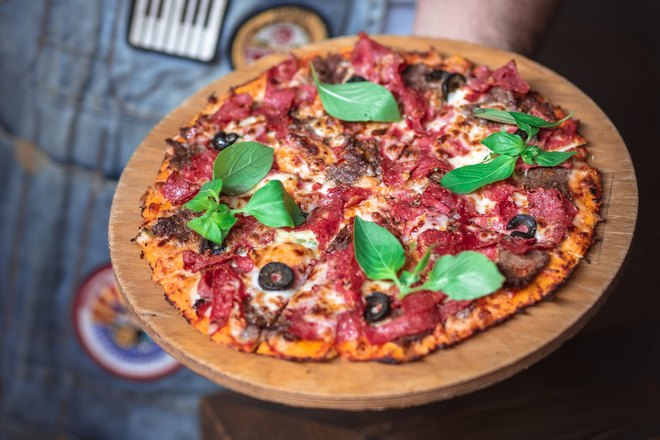 Блюдо с пиццей держат в левой руке