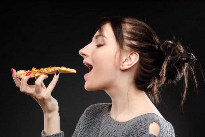 Девушка держит кусочек пиццы