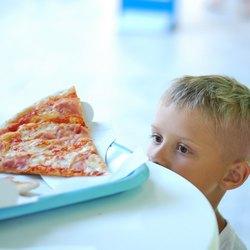 Мальчик смотрит на кусочек пиццы