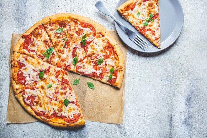 Почти целая пицца и один кусочек на тарелке с вилкой
