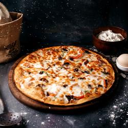 Румяная пицца и маленькая емкость с мукой