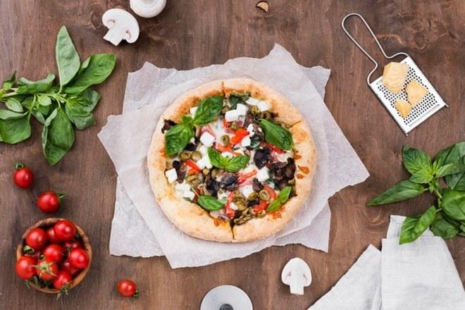 Пицца в окружении грибов и томатов