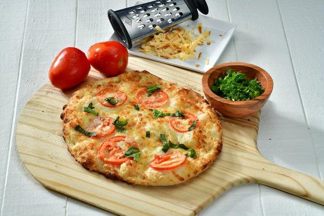 Пицца, сыр, зелень и помидоры