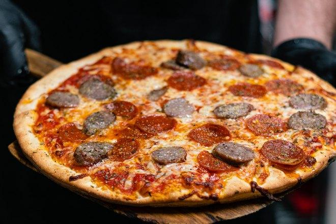 Пицца в руках пекаря
