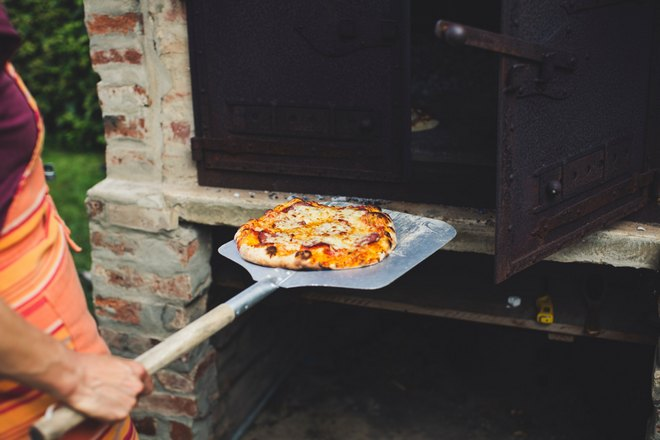 Пицца на лопатке возле печи